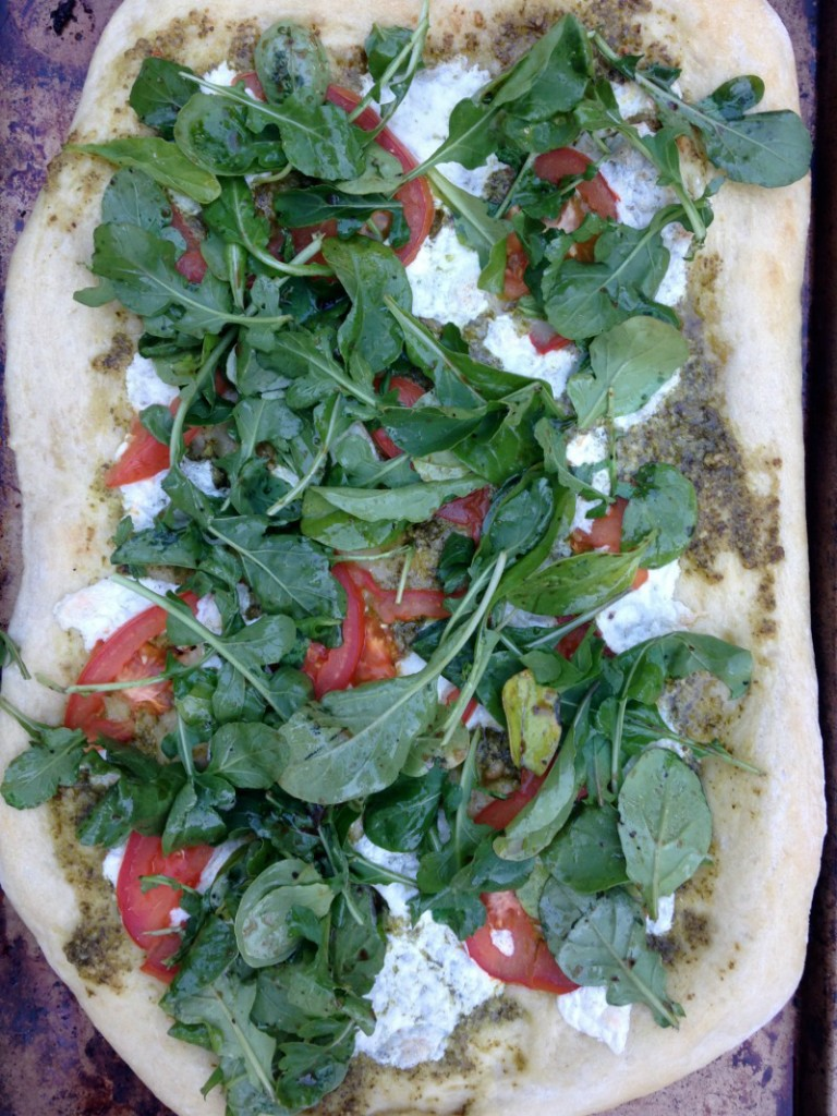 Arugula, fresh tomatoes, pesto, and buffalo mozzarella on top of pizza crust.