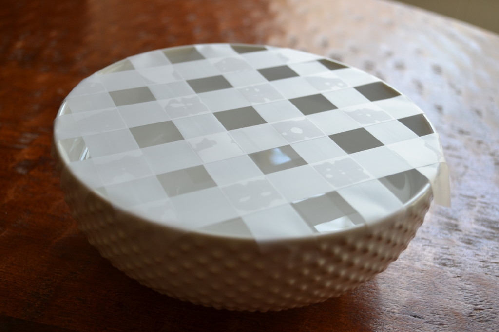 A white bowl with a lattice pattern of tape over the top, used to hold flowers in place.
