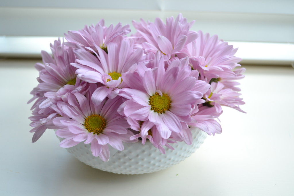 Lavender flowers arranged in a white bowl.