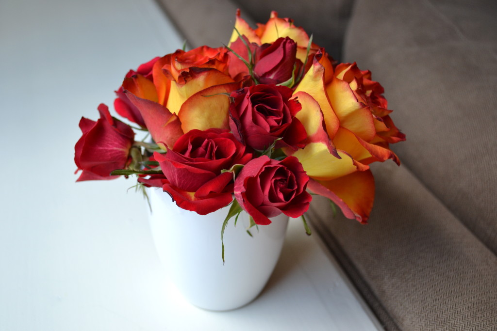 Small arrangement of roses in a white mug.