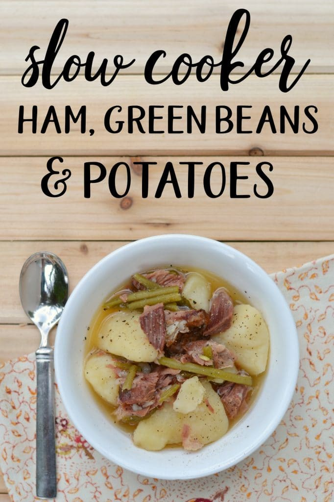 Bowl of ham, green beans & potatoes on a wooden board