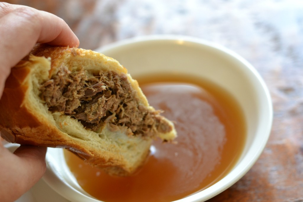 French Dip sandwich being dunked into au jus.