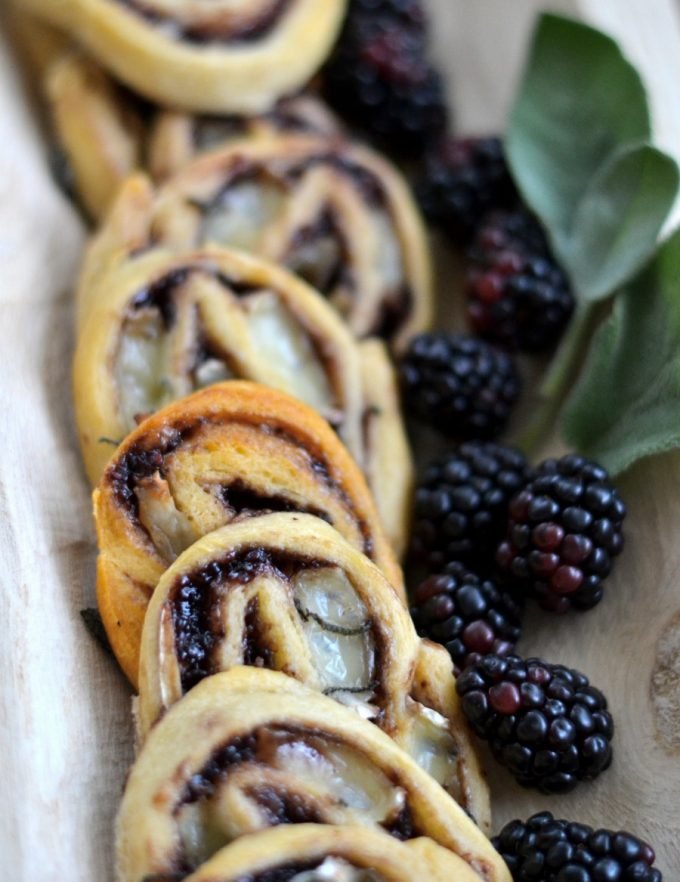 Brie and blackberry jam pinwheels on a wooden tray adorned with fresh blackberries and sage leaves.