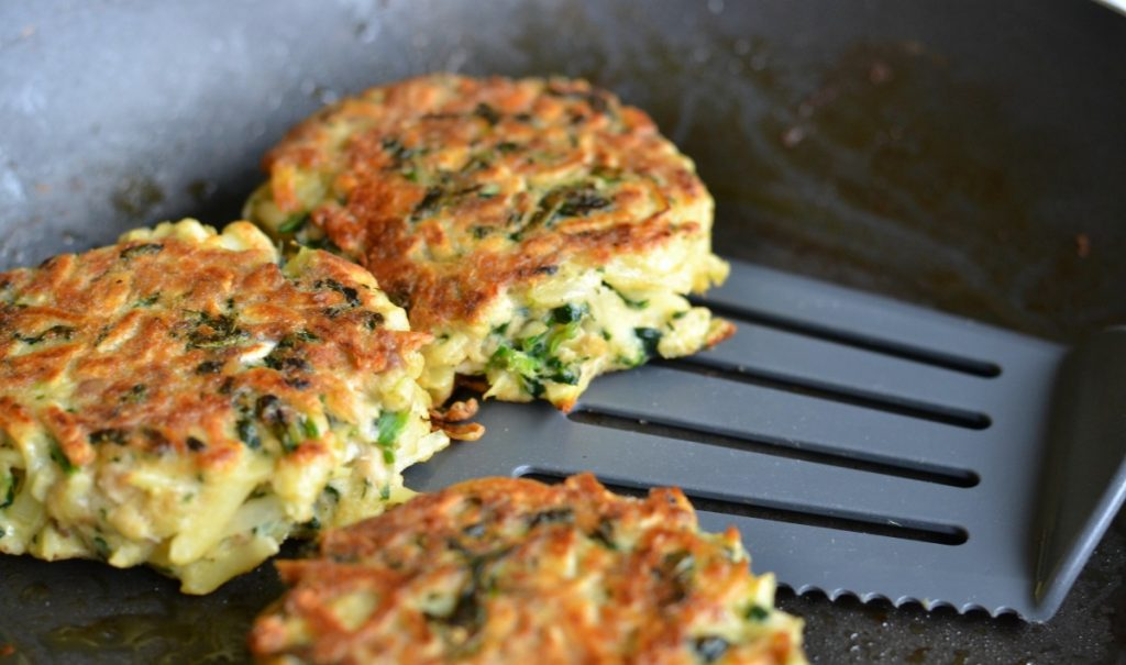 Salmon patties being pan fried in a skillet