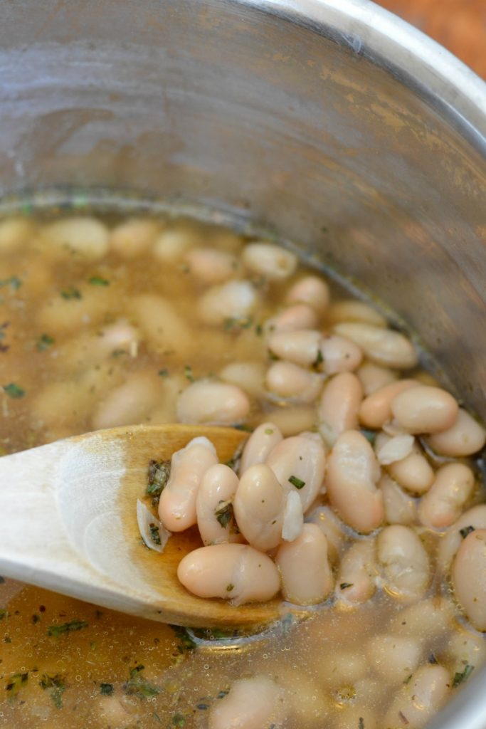 White beans simmering in a stainless steel pot