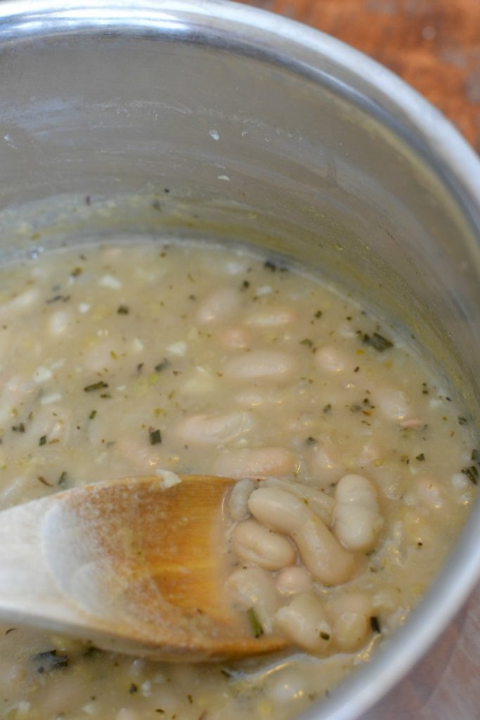 Beans are lightly smashed with a wooden spoon to thicken the broth