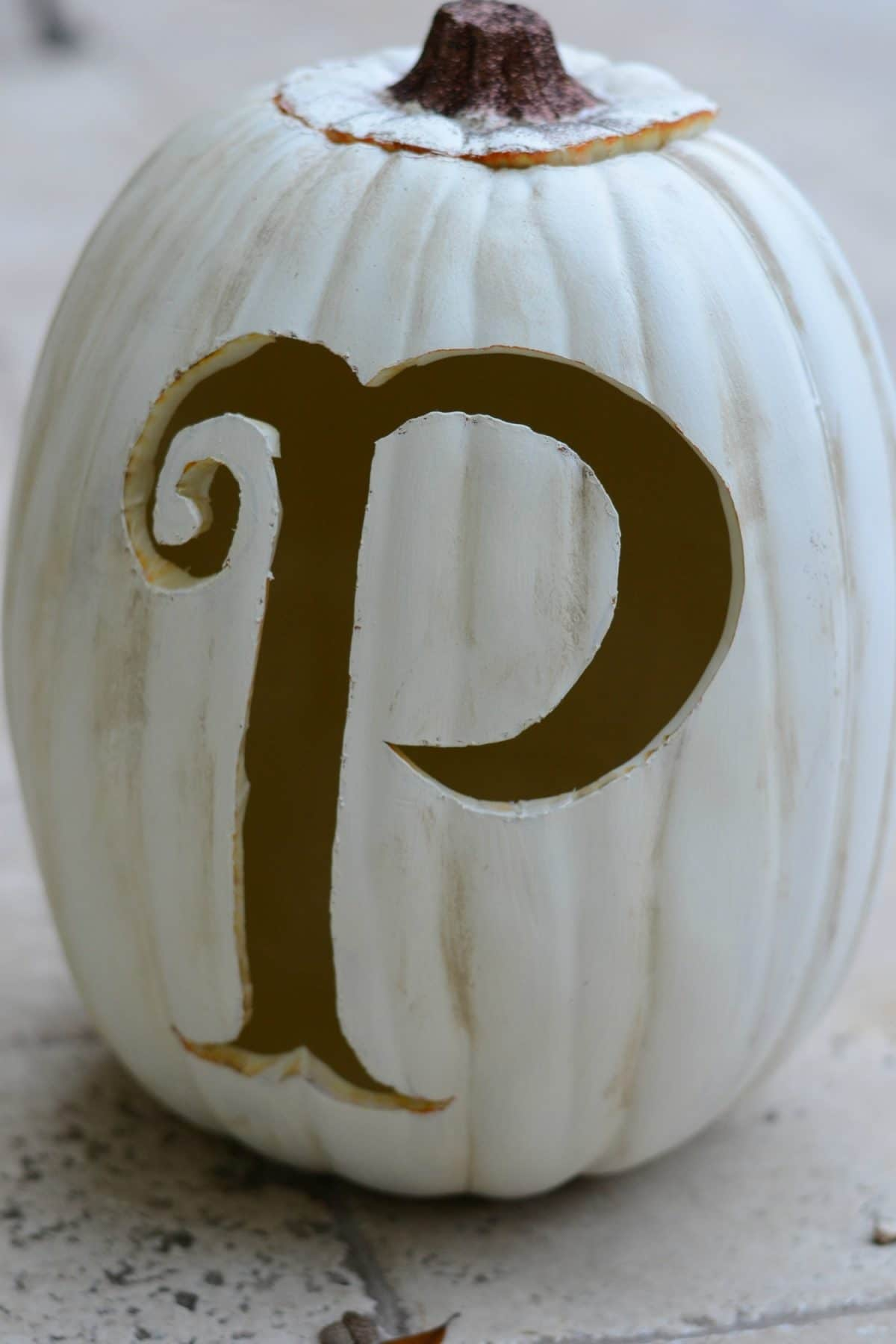 Letter P carved into a large craft pumpkin.