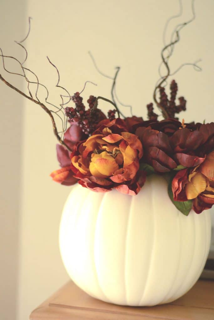 Faux flowers and stems in a vase made from a white craft pumpkin.
