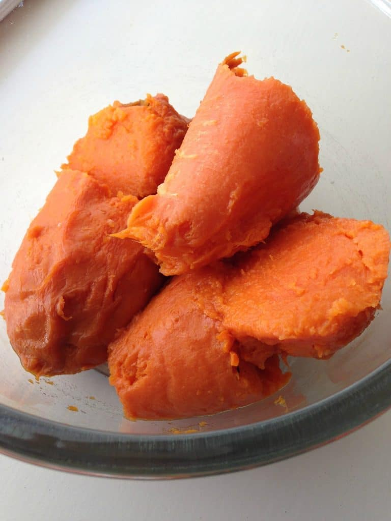Peeled, baked sweet potatoes in a glass bowl
