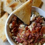 Baked goat cheese dip on a tray with toasted bread