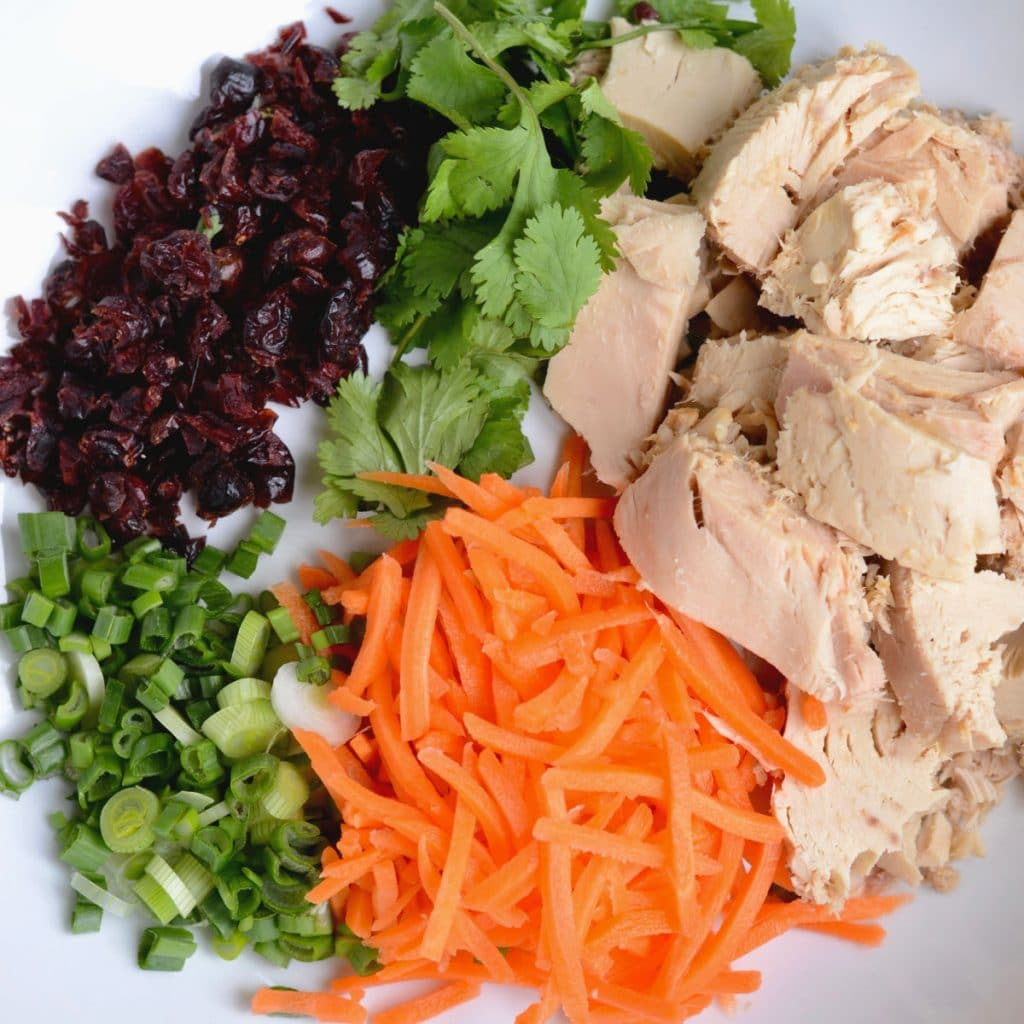 Ingredients for Asian tuna salad, including carrots, tuna, cilantro, green onion, and craisins