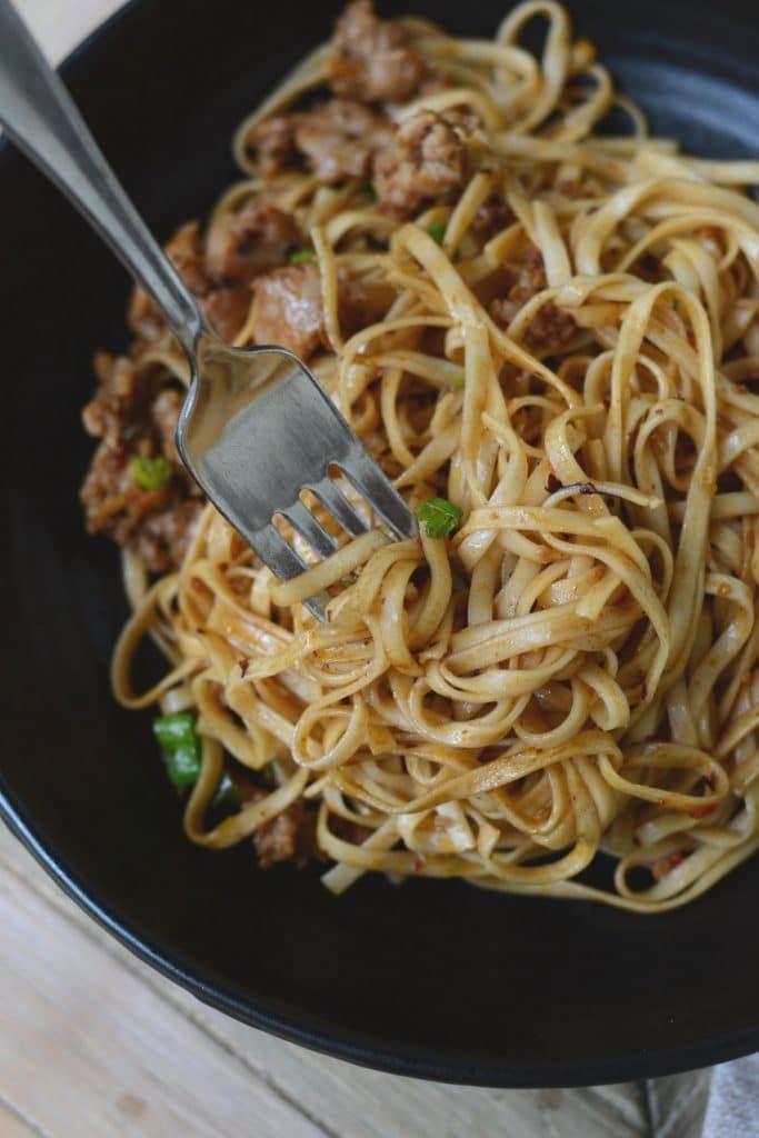 Pork and egg noodles in a black bowl