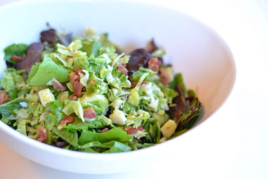 Chopped brussels sprouts salad in a white bowl.