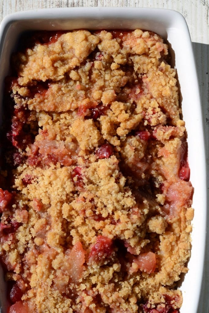 Baked cranberry apple dessert in a white baking dish.