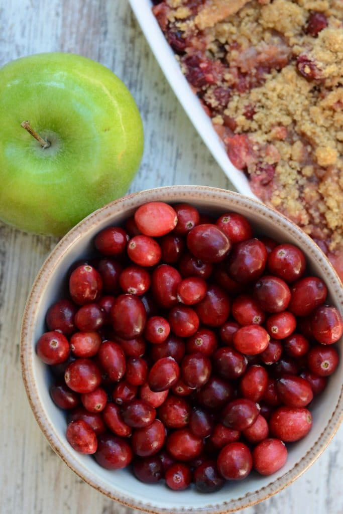 Fresh cranberries in a bowl with a Granny Smith apple