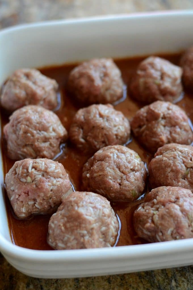 Uncooked porcupine meatballs in a baking dish.