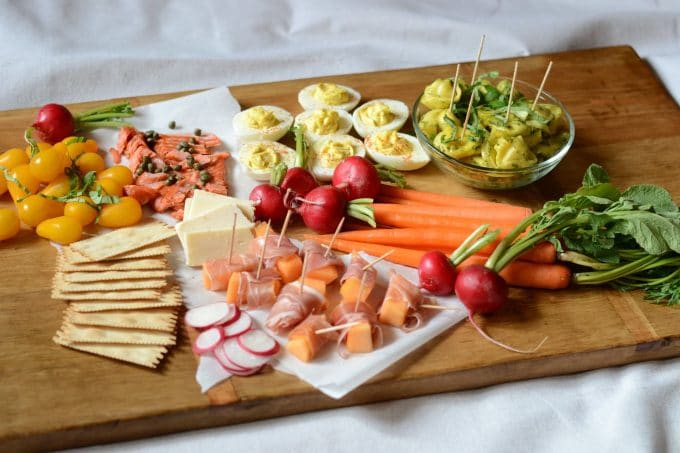 Wooden tray with seasonal vegetables, cheese and appetizers